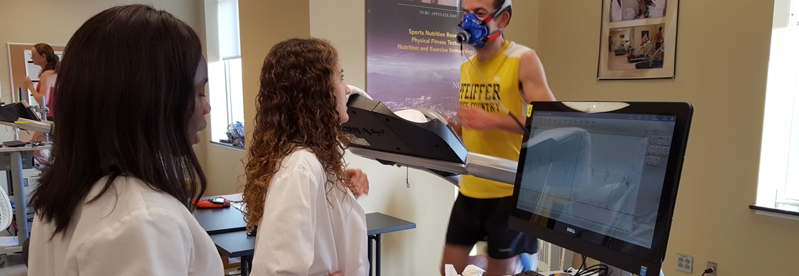 Students talking with an athlete on a treadmill in the Human Performance Lab