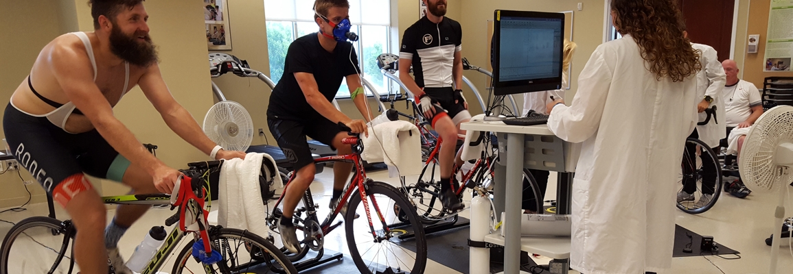A student working with cyclists in the Human Performance Lab