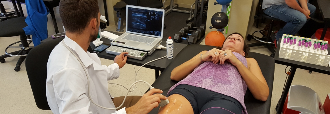 A student assessing an athlete in the Human Performance Lab
